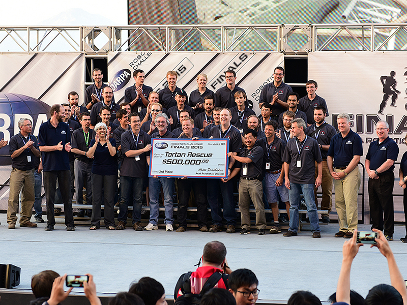 National Robotics Engineering Center (NREC) group celebrates with giant check.